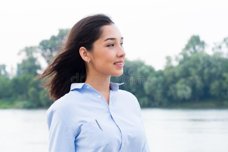 Stående åt sidan för Closeup av den härliga asiatiska brunettkvinnan som bär den blåa skjortan på naturbakgrund royaltyfria foton