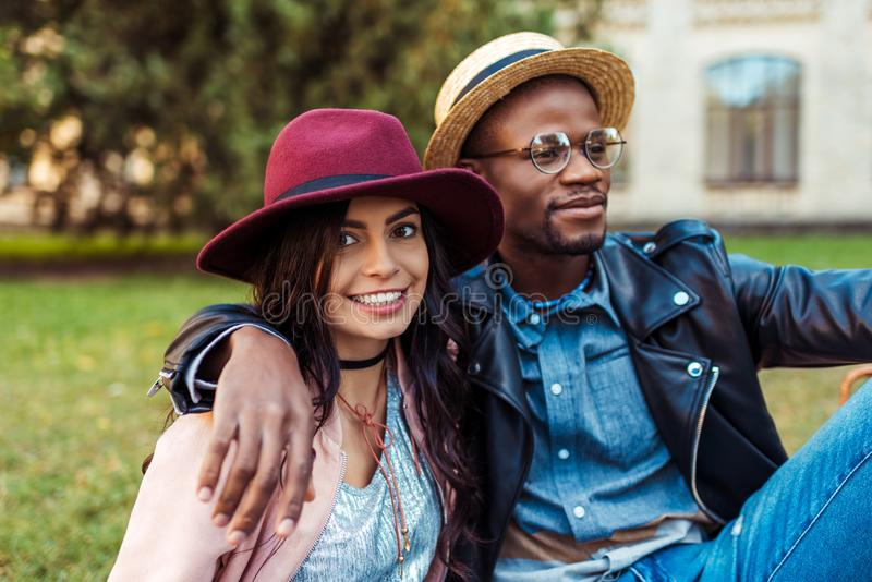 Stående av älskvärda mellan skilda raser par i hattar som sitter på ett gräs i fotografering för bildbyråer