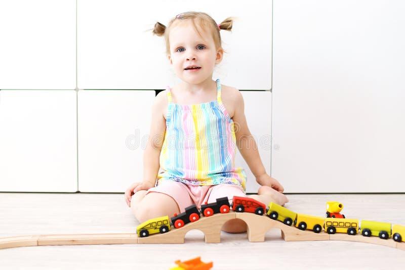 Stående av älskvärda små 2 år flicka som spelar leksakträrailro royaltyfria foton