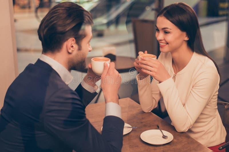 Stående av älskvärt romantiskt parsammanträde i ett kafé med kaffe royaltyfria foton