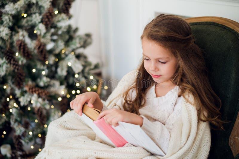 Stående av 7 år gammal barnläsebok hemma på jul royaltyfri bild