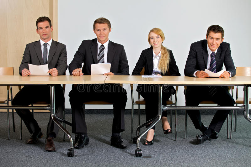 Stående av affärsfolk som i regeringsställning sitter royaltyfri foto