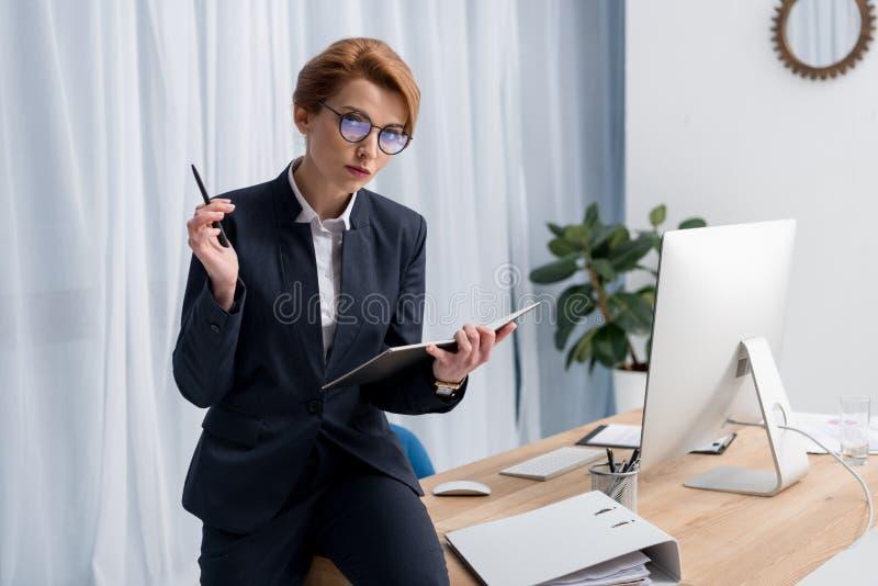 stående av affärskvinnan i glasögon med anteckningsboken på arbetsplatsen royaltyfri foto