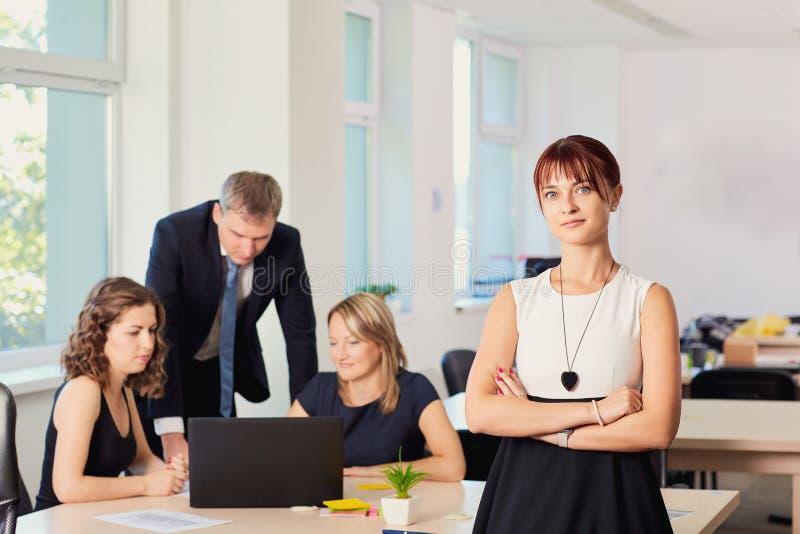 Stående av affärskvinnan i kontoret i en stol på bakgrunden av funktionsdugliga affärspartners arkivfoto