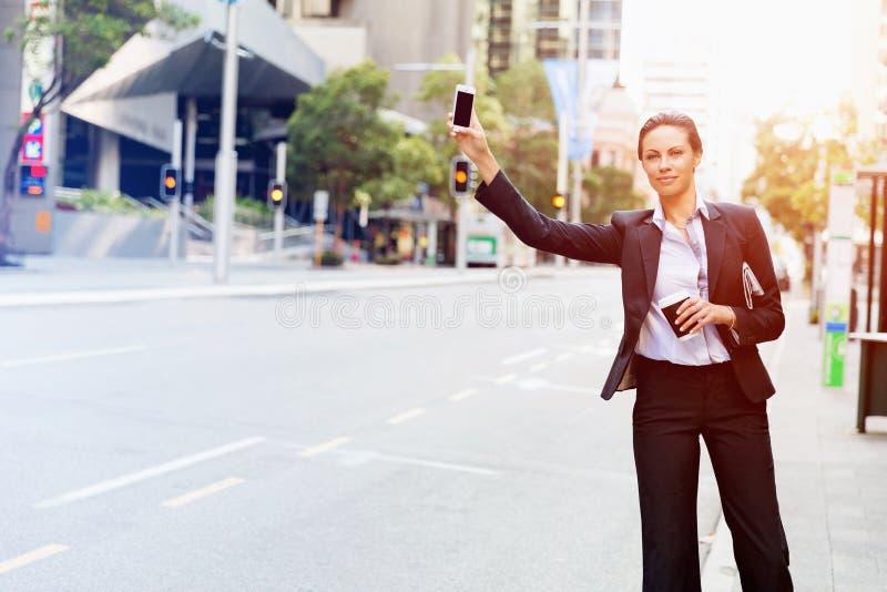 Stående av affärskvinnan som fångar taxien royaltyfria bilder