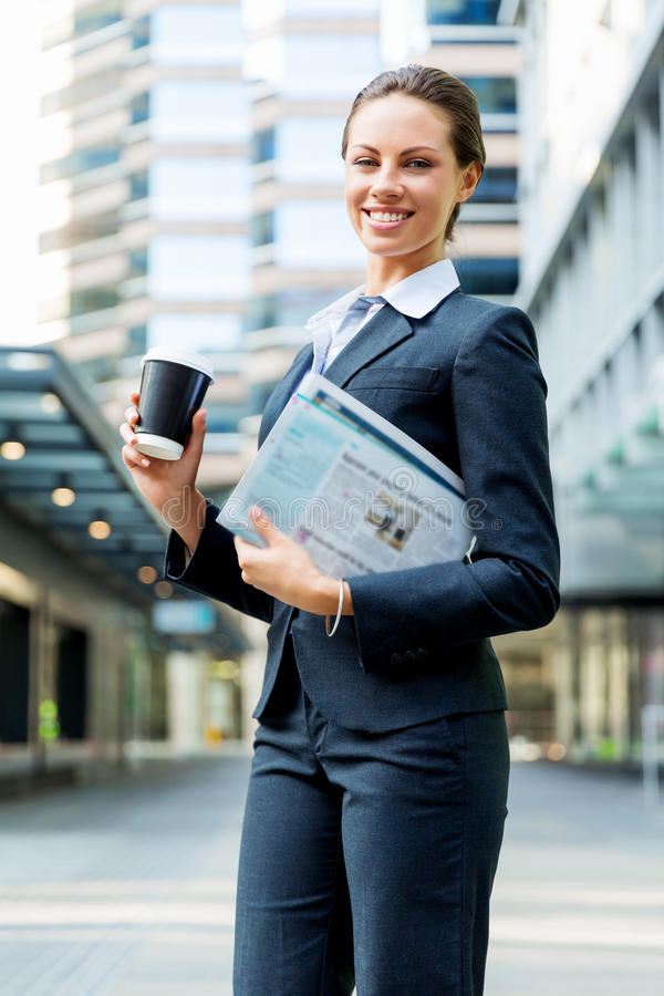Stående av affärskvinnan som går och ler som är utomhus- royaltyfria bilder