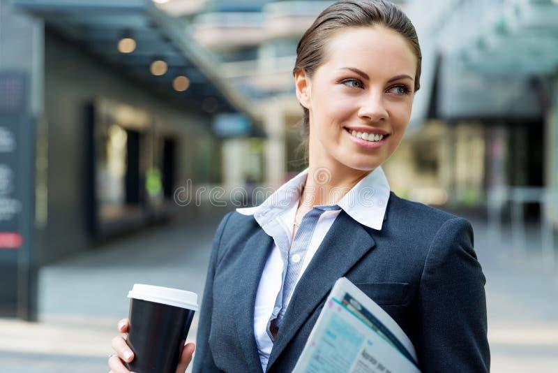Stående av affärskvinnan som går och ler som är utomhus- arkivfoto