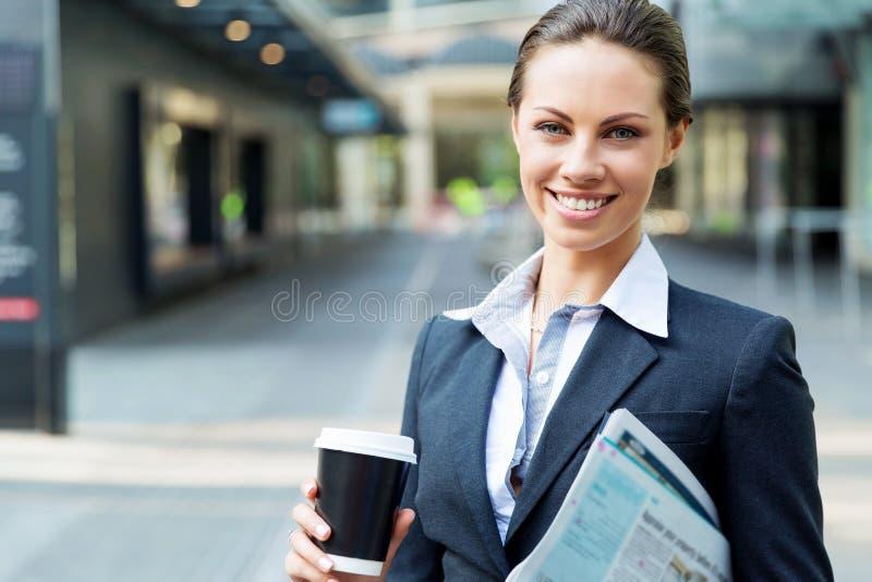Stående av affärskvinnan som går och ler som är utomhus- royaltyfri foto