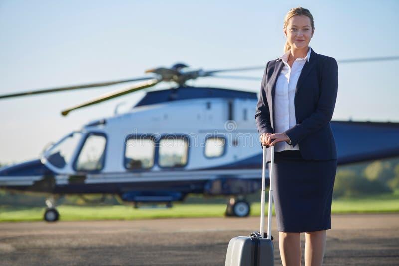 Stående av affärskvinnan Standing In Front Of Helicopter arkivbild