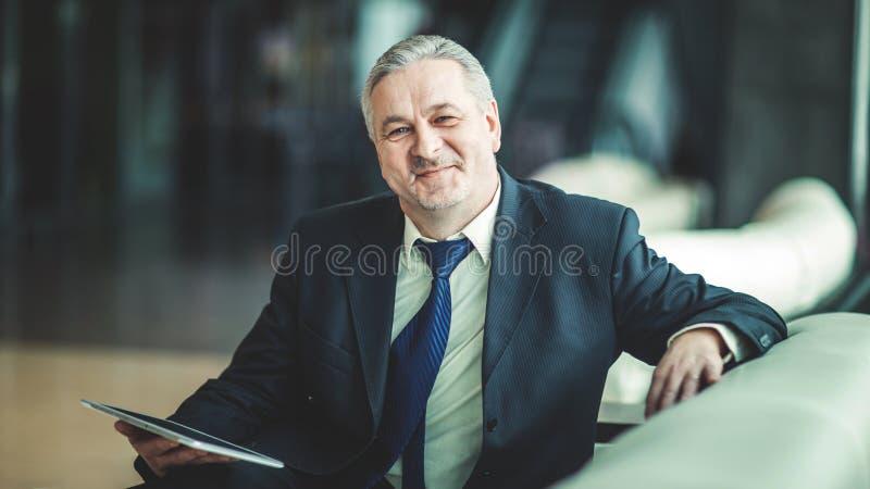 Stående av affärsmannen med digitalt minnestavlasammanträde i stolen framme av kontoret royaltyfri bild