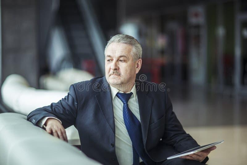 Stående av affärsmannen med digitalt minnestavlasammanträde i stolen framme av kontoret fotografering för bildbyråer