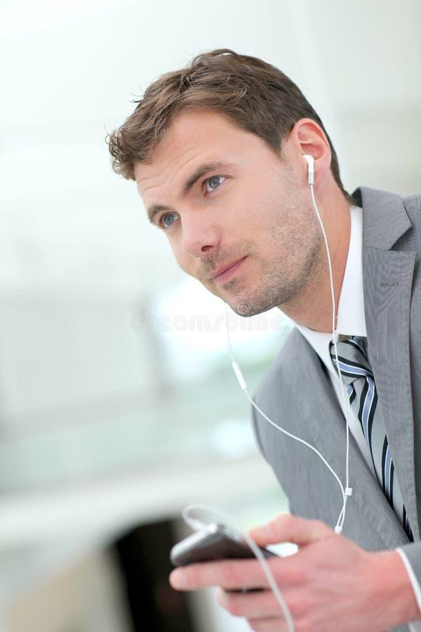 Stående av affärsmannen med hörlurar som talar på telefonen royaltyfria bilder