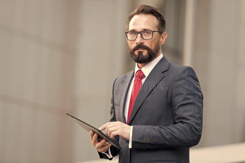 Stående av affärsmannen med minnestavlan i hand på bakgrund av kontorsbyggnad Affärsman som använder hans minnestavla ut ur konto arkivfoto