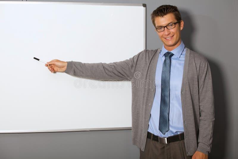Stående av affärsmannen som i regeringsställning pekar på whiteboarden arkivbild