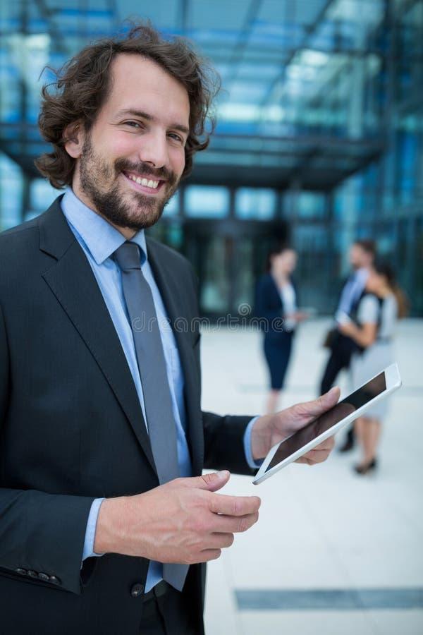 Stående av affärsmannen som rymmer den digitala minnestavlan royaltyfria foton