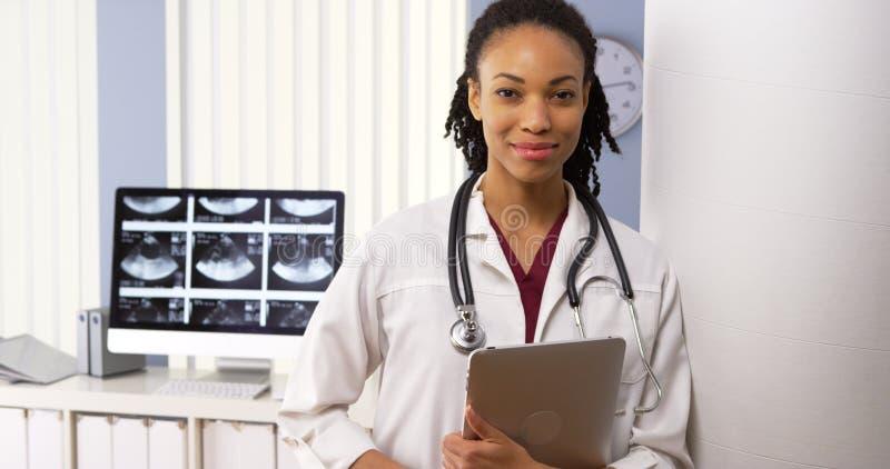 Stående av afrikansk amerikankvinnadoktorn som ler i sjukhus arkivfoto