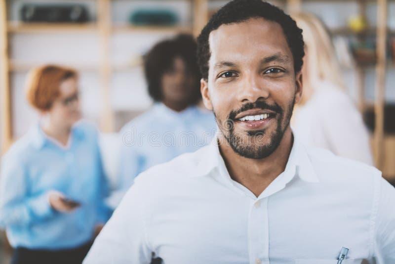 Stående av afrikansk amerikanmannen som ser och ler på kameran Affärslag på en bakgrund i modernt kontor royaltyfri bild