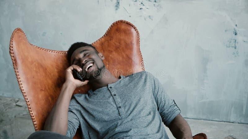 Stående av afrikanskt mansammanträde i stolen och samtal på Smartphone Mannen skrattar på skämtet och att ha stor tid royaltyfria bilder