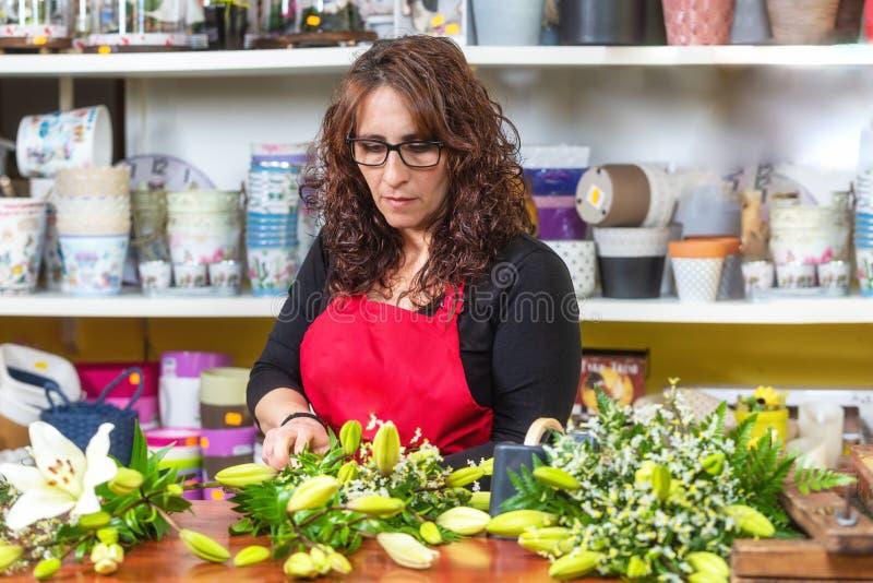 Stående av anseendet för förkläde för kvinnablomsterhandlare det bärande på räknaren som gör buketten för klient på blomsterhande royaltyfria bilder