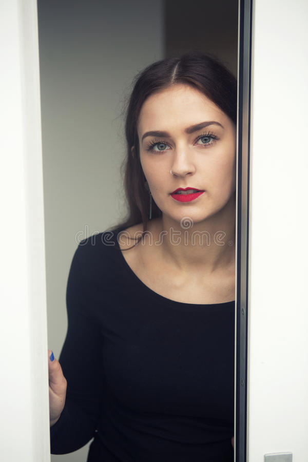 Stående av anseendet för ung kvinna vid det öppna fönstret fotografering för bildbyråer