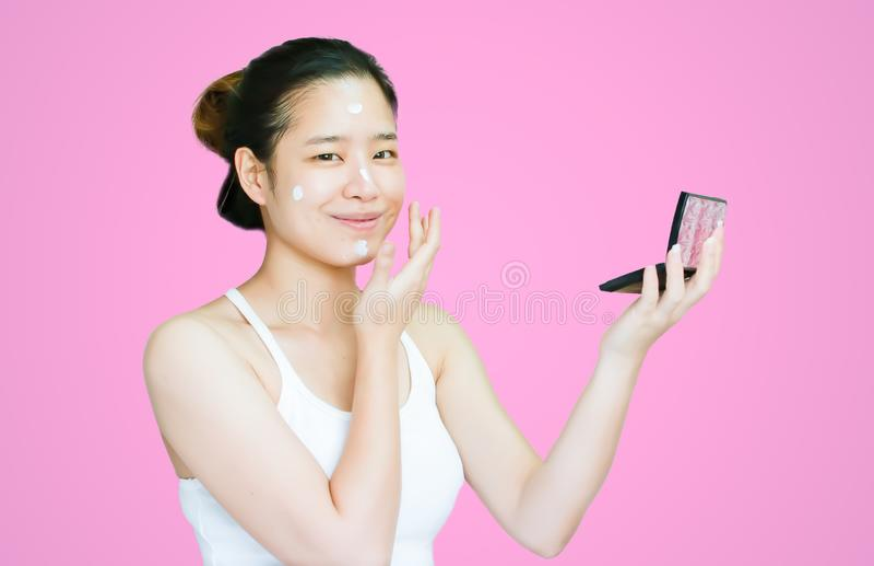 Stående av asiatet som sätter lotionkräm på hennes framsida arkivfoto