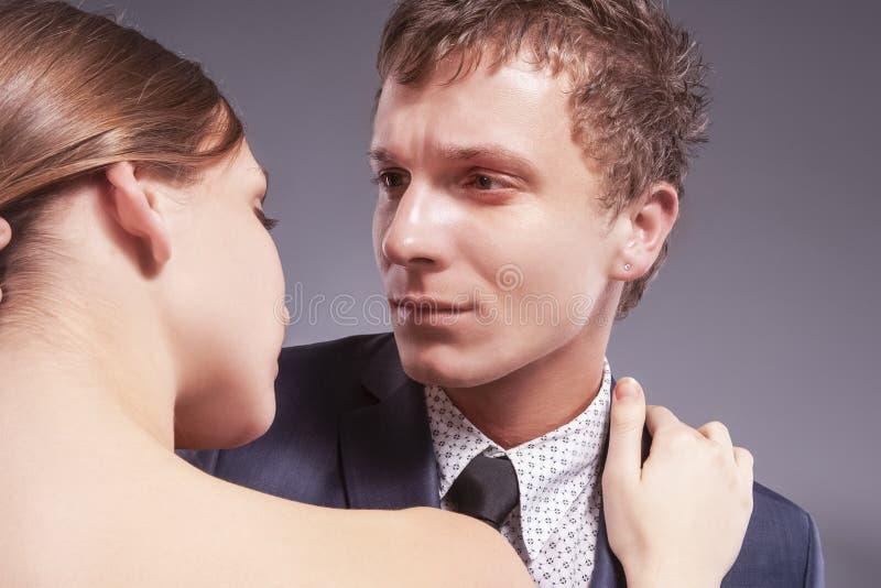 Stående av att älska Caucasian par som tillsammans poserar Mot gr? f?rger fotografering för bildbyråer