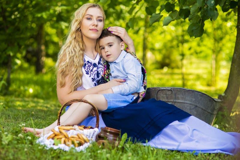 Stående av att älska den Caucasian modern med hennes lilla unge Posera med korgen som är full av brödcirklar utomhus royaltyfri fotografi