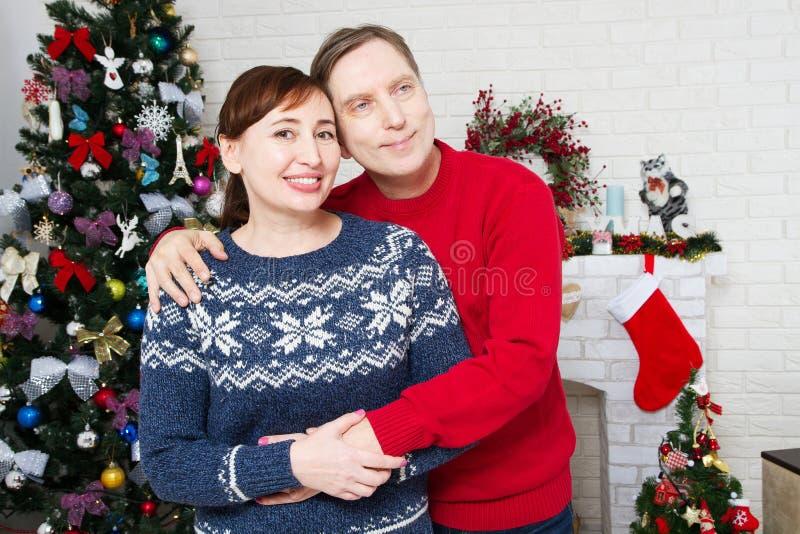 Stående av att älska mellersta åldriga par i vardagsrum med julträdet och den dekorerade spisen som älskar familjen arkivbild