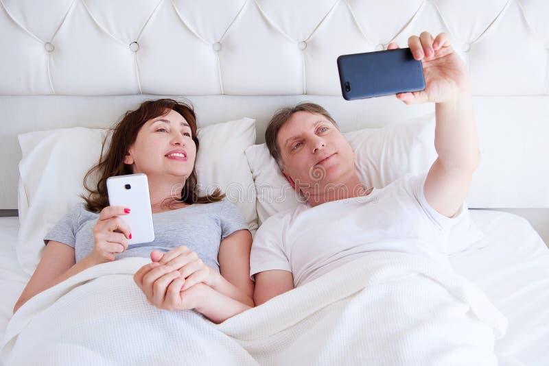 Stående av att älska mellersta åldriga par som ler och att göra selfie på smartphonen i sovrummet, lycklig familj royaltyfria foton