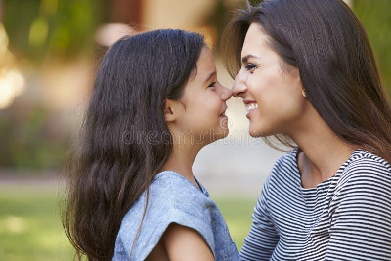 Stående av att älska modern och dottern i trädgård arkivbild