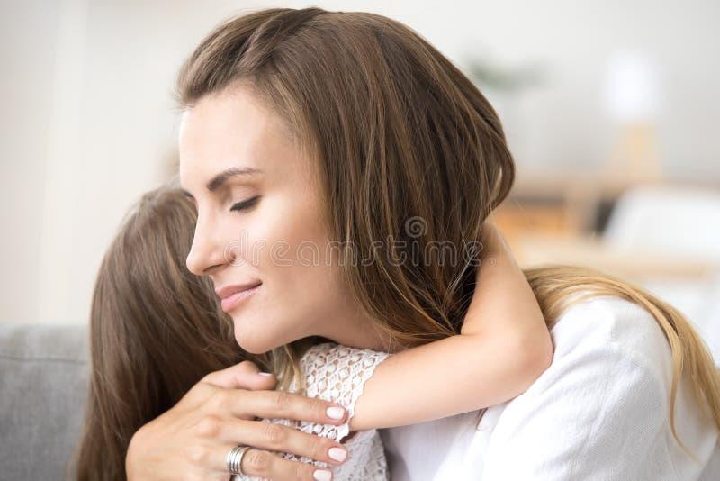 Stående av att älska modern som omfamnar den lilla dottern royaltyfri fotografi