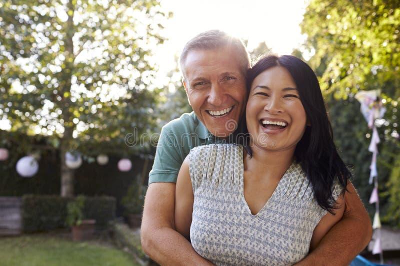 Stående av att älska mogna par i bakgårdträdgård royaltyfria foton