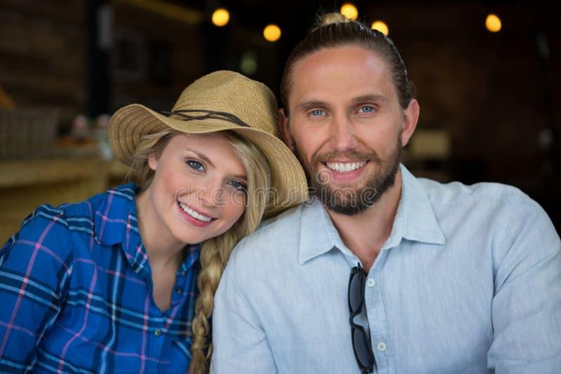 Stående av att älska par som ler i coffee shop royaltyfri bild
