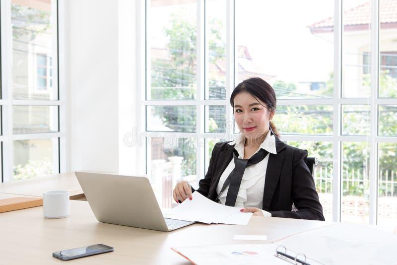 Stående av att charma asia som är businesslady på kontorsskrivbordet Damsekreterare arkivfoto
