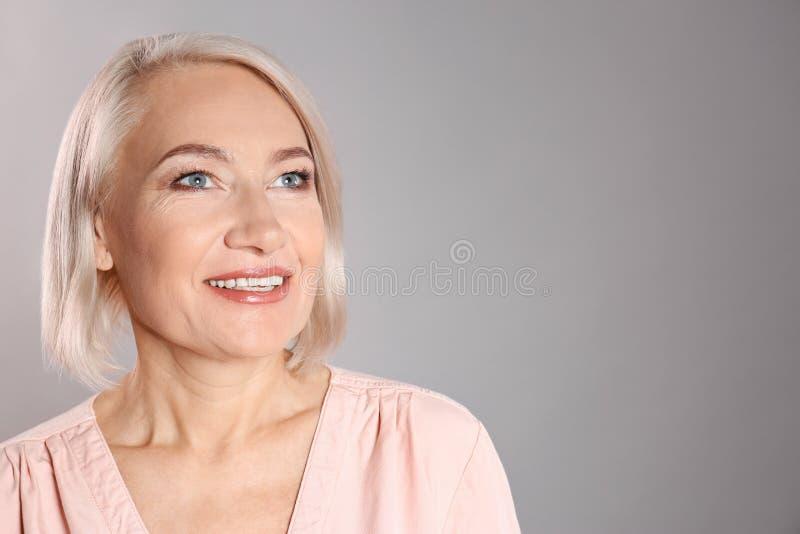 Stående av att charma den mogna kvinnan med härlig framsidahud och naturlig makeup på grå bakgrund, utrymme för text royaltyfria bilder