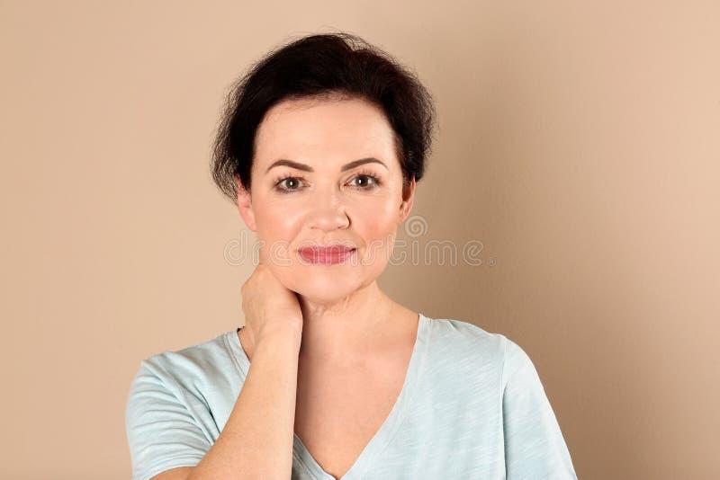 Stående av att charma den mogna kvinnan med sund framsidahud och naturlig makeup på beige bakgrund royaltyfri fotografi