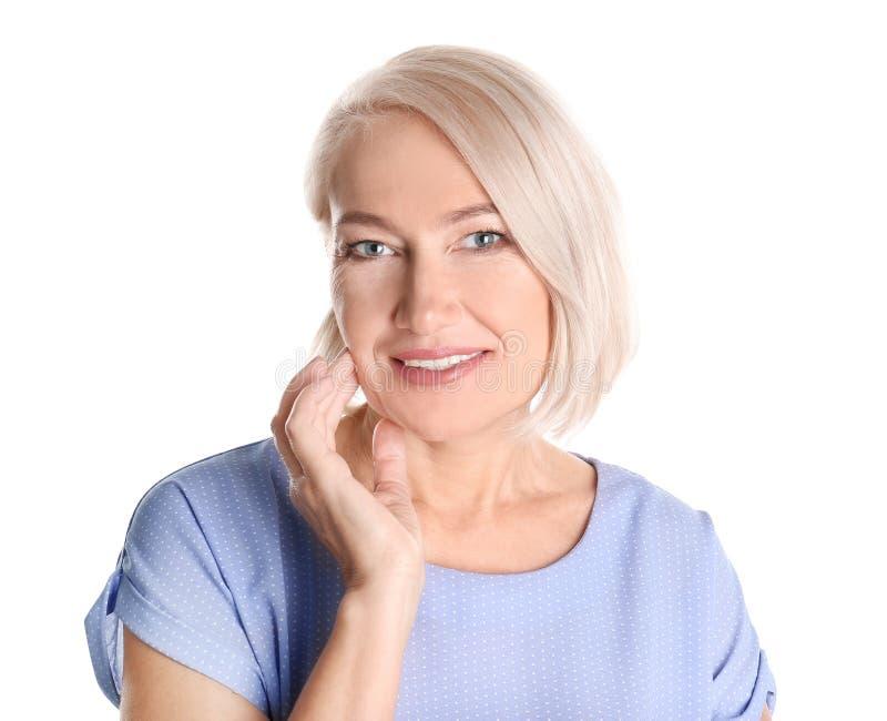 Stående av att charma den mogna kvinnan med sund framsidahud och naturlig makeup på vit bakgrund royaltyfri bild