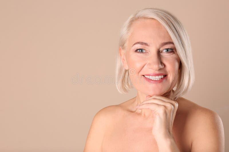 Stående av att charma den mogna kvinnan med sund härlig framsidahud och naturlig makeup på beige bakgrund arkivbild
