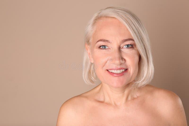 Stående av att charma den mogna kvinnan med sund härlig framsidahud och naturlig makeup på beige bakgrund arkivbilder