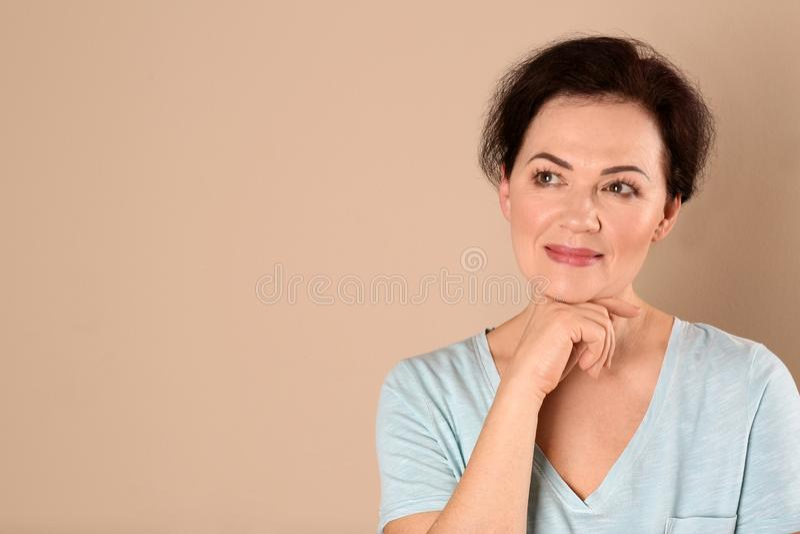 Stående av att charma den mogna kvinnan med sund härlig framsidahud och naturlig makeup på beige bakgrund royaltyfria foton