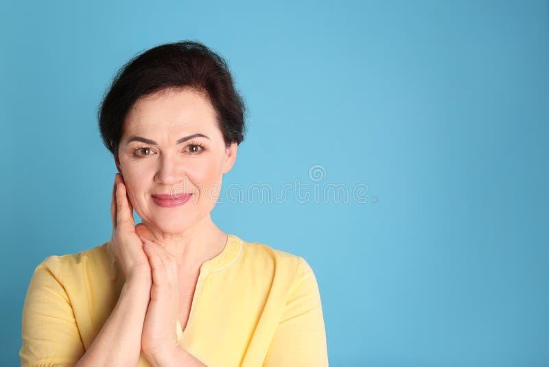 Stående av att charma den mogna kvinnan med sund härlig framsidahud och naturlig makeup på blå bakgrund royaltyfria bilder