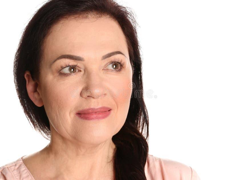 Stående av att charma den mogna kvinnan med sund härlig framsidahud och naturlig makeup på vit bakgrund arkivfoto
