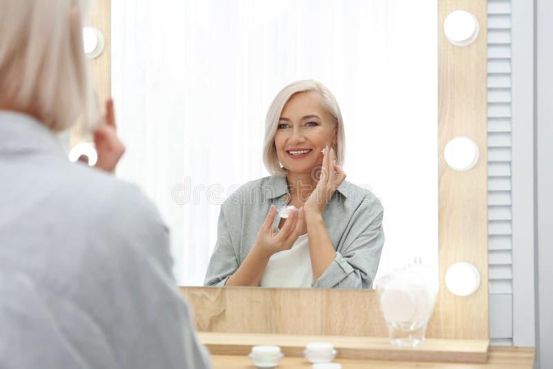 Stående av att charma den mogna kvinnan med sund härlig framsidahud och naturlig makeup som applicerar kräm fotografering för bildbyråer
