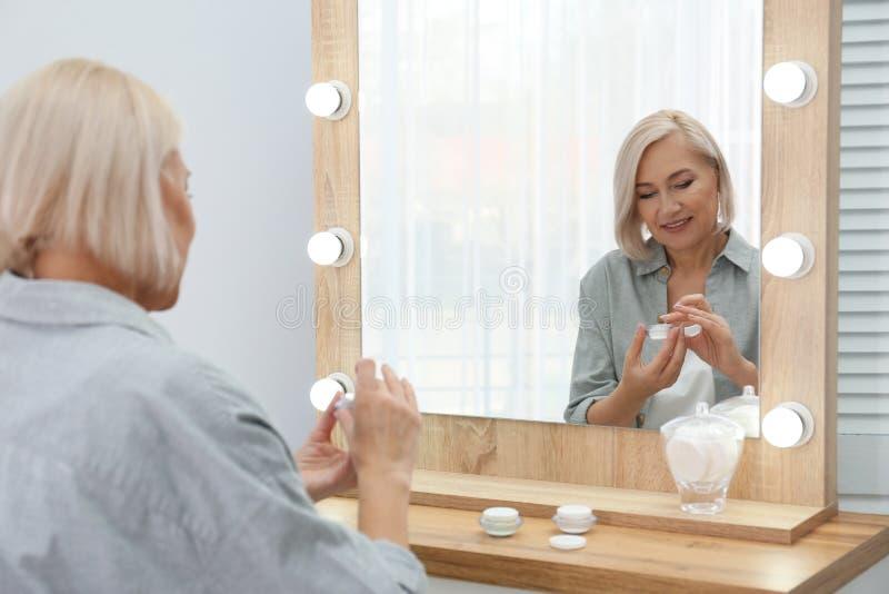 Stående av att charma den mogna kvinnan med sund härlig framsidahud och naturlig makeup som applicerar kräm royaltyfri fotografi