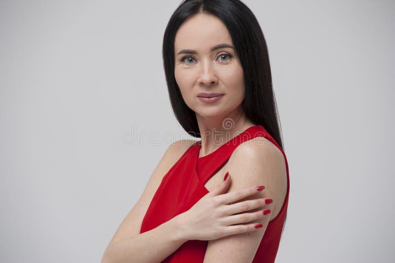Stående av att charma den unga brunettkvinnan som bär den röda blusen royaltyfri foto