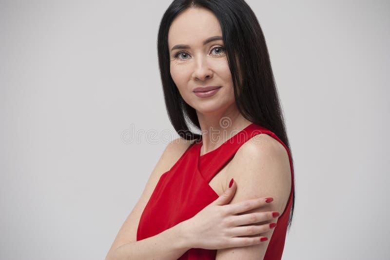 Stående av att charma den unga brunettkvinnan som bär den röda blusen royaltyfri fotografi