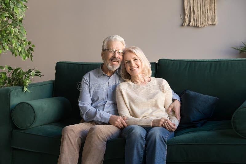Stående av att krama den åldriga mannen och kvinnan, familj som sitter på soffan fotografering för bildbyråer