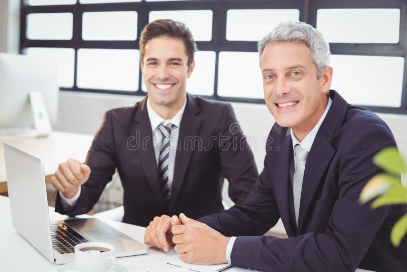Stående av att le affärsfolk med bärbara datorn arkivbild