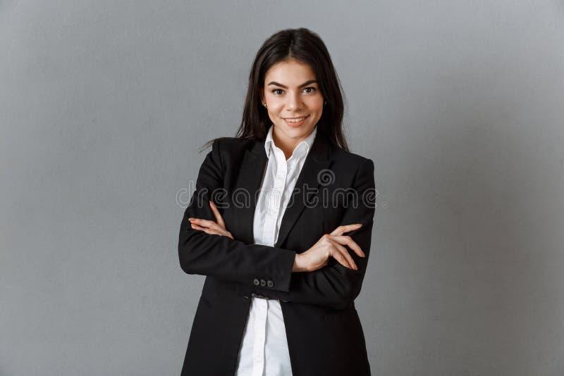 stående av att le affärskvinnan i dräkt med armar som korsas mot grå färger arkivbild
