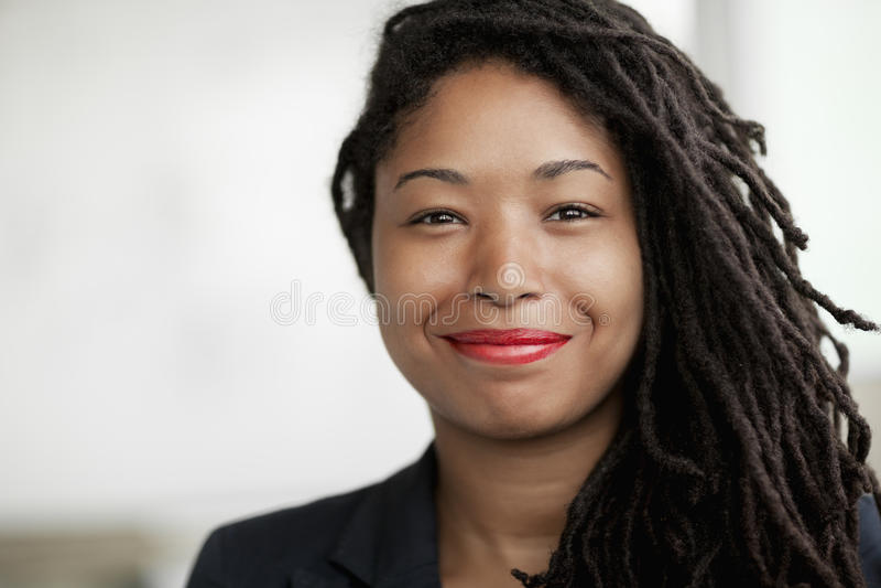Stående av att le affärskvinnan med dreadlocks, head och skuldror royaltyfri fotografi